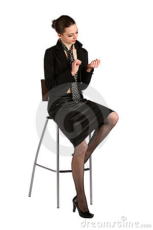 Girl in black suit sits on stool.