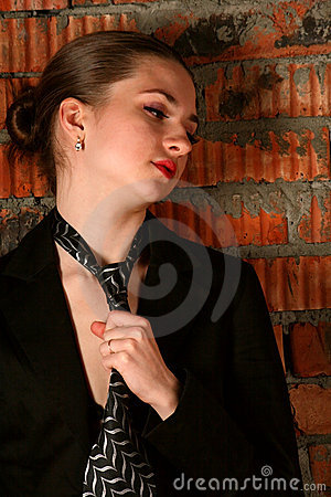 Girl in black suit tuck her necktie.