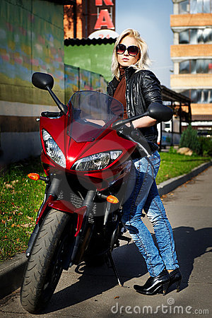 The girl blonde about a red motorcycle