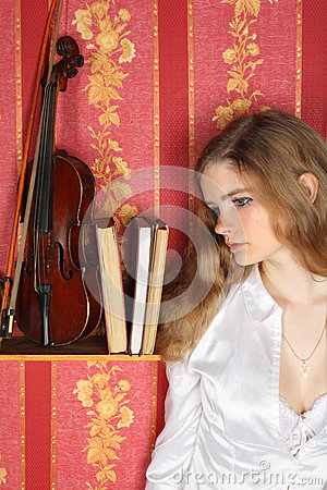 Girl in blouse in room near violin
