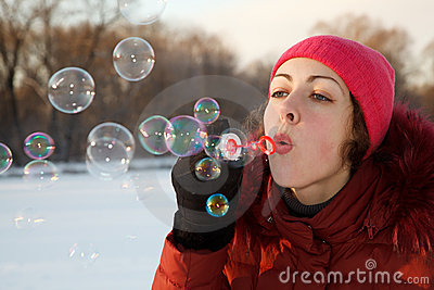 Girl blow bubbles in winter park.
