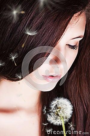 Girl blowing on dandelion.