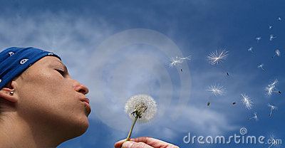 Girl blowing seeds out of a dandelion