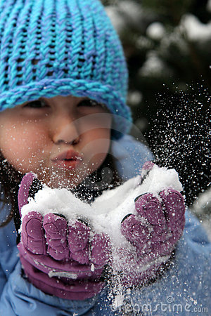 Girl blowing snow from gloves