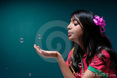 Girl blowing soap bubble