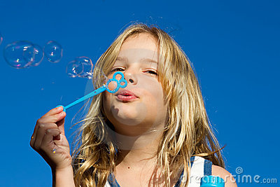 Girl blows bubbles against blue sky