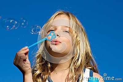 Girl blows bubbles against blue sky