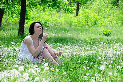 The girl blows on a dandelion