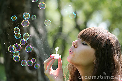 Girl blows soap bubbles
