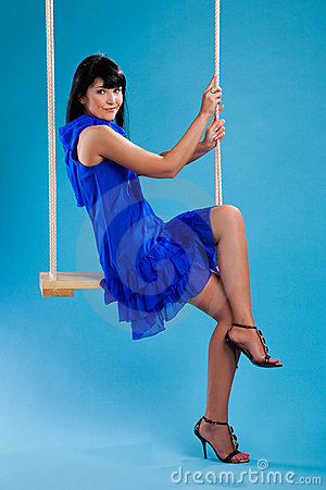Girl in the blue dress sitting on swings