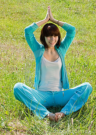 Girl in   blue exercising on meadow