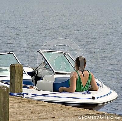 Girl in boat tied to dock