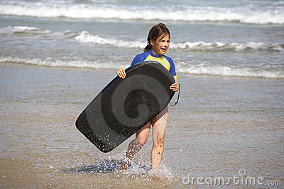 Girl with boogie board at beach