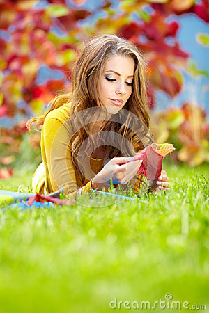 Girl with book in the autumn park