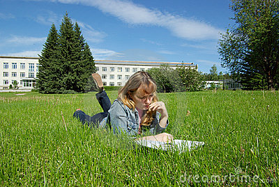 Girl with book lying on grass