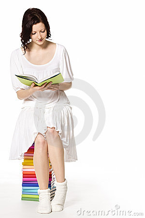 Girl on book stack reading.