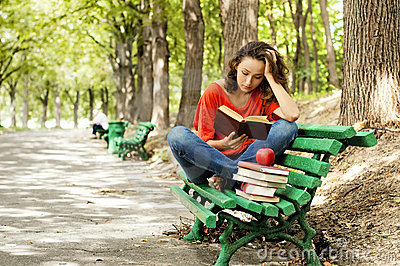 The girl with books sitting on a bench