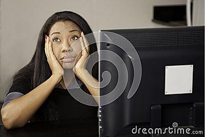 Girl bored at computer.