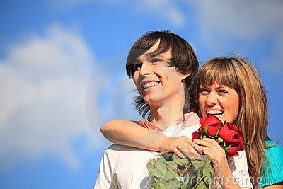 Girl with bouquet of roses embraces behind guy