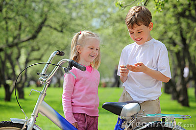 Girl, boy and  bicycle in park