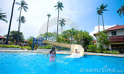 Girl and boy enjoying the slide by swimming pool