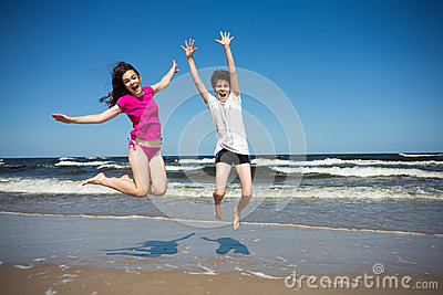 Girl and boy jumping on beach