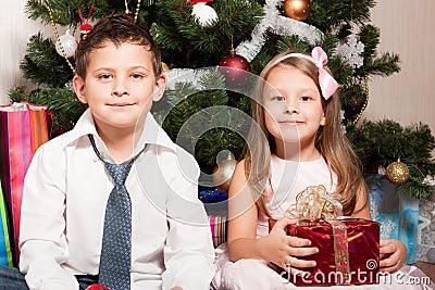 Girl and boy near a fir-tree