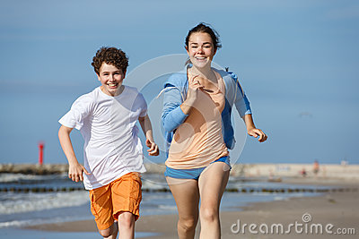 Girl and boy running on beach