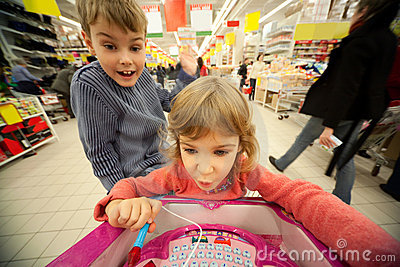 Girl and boy sit in shoppingcart, play new toy