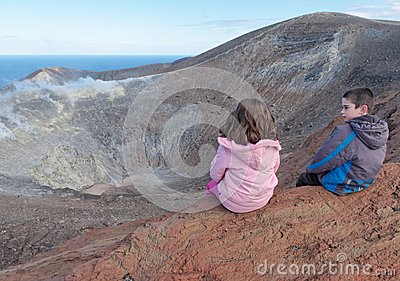 Girl and boy sitting on the rim of volcano crater