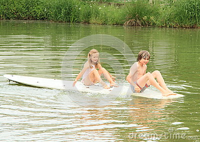 Girl and boy sitting on surf Stock Photo