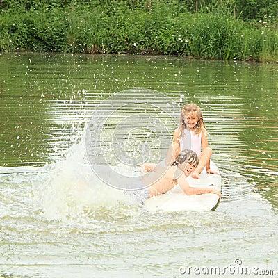 Girl and boy splashing on surf