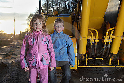 Girl and boy standing near crawler tractor