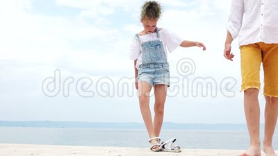 Girl and boy standing on a sea berth. Girl takes off her sandals and goes barefoot, summer vacation, happy children.  stock footage