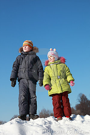 Girl and boy standing at snow
