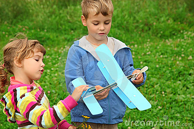 Girl and boy with toy airplane in hands