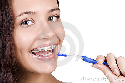 Girl with braces brushing her teeth