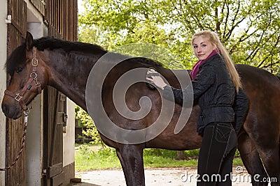 Girl brushes her pony