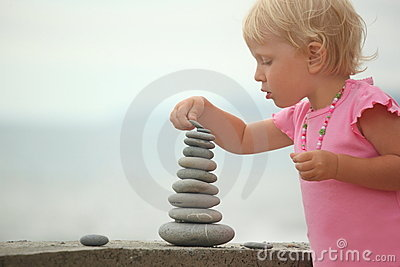 Girl is building a construction from pebble stones
