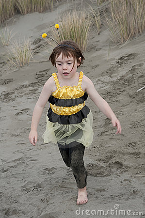 Girl in bumble bee costume playing at beach
