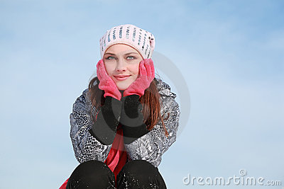 Girl in cap squatting and holds hands on cheeks