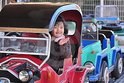 A girl on a car in an amusement park