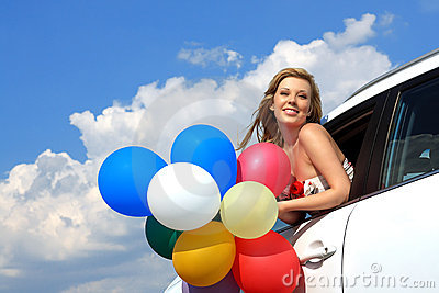 Girl in the car with colorful balloons