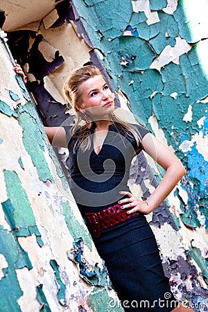 Girl in case dress stay near wall
