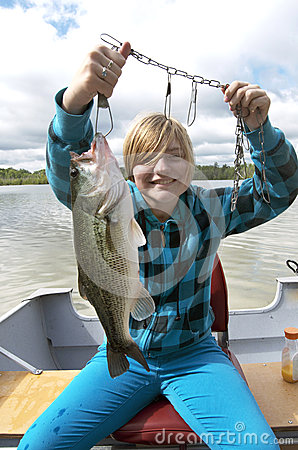 Girl Catching Big Bass In Boat On Lake