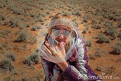 Girl and chameleon in the desert