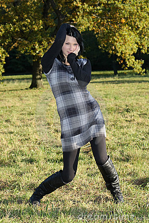 Girl in checkered dress posing in autumn park