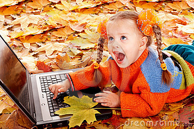 Girl child in autumn orange leaves with laptop.
