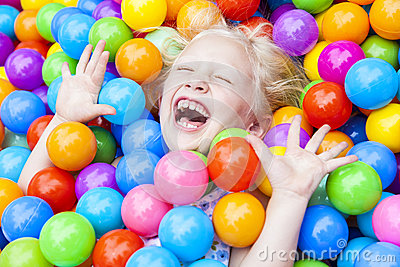 Girl Child Having Fun Playing in Colored Balls