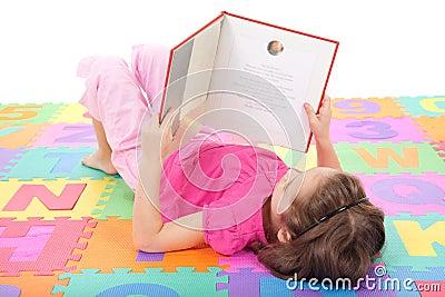 Girl child reading kids book on alphabet